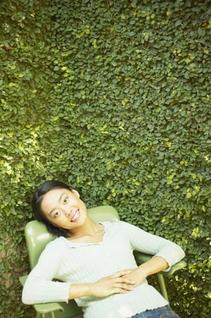 chirpy: High angle view of a young woman sitting on a chair outdoors smiling