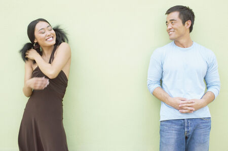 way of behaving: Young woman and a mid adult man standing against a wall smiling