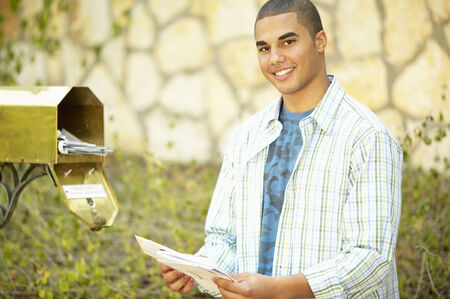 german ethnicity: Portrait of a young man taking out mail from a mail box