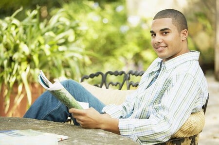 hold ups: Portrait of a young man sitting at a table holding a magazine