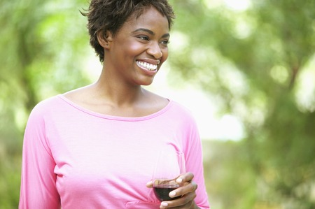 hold ups: Young woman smiling holding a glass of red wine
