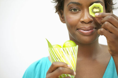 hold ups: Portrait of a young woman holding a slice of kiwi fruit over her eye