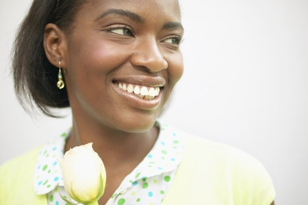 hold ups: Young woman smiling holding a rose LANG_EVOIMAGES
