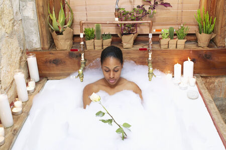 woman in bath: Young woman in a bubble bath LANG_EVOIMAGES