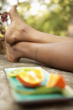 hold ups: Woman lying besides a plate with a sliced orange LANG_EVOIMAGES