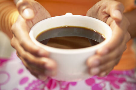 restfulness: Close-up of a young woman holding a cup of coffee