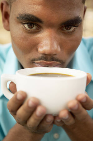 hold ups: Portrait of a young man holding a cup of coffee