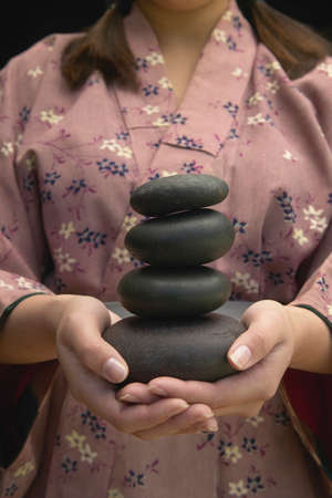 anecdote: Young woman holding a pile of black stones