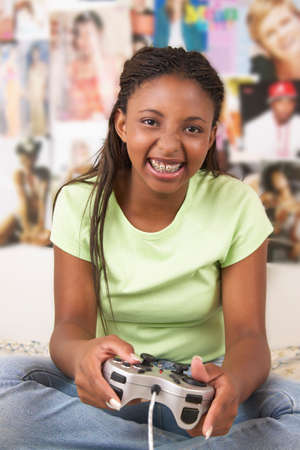 middle eastern ethnicity: Portrait of a teenager girl sitting on a bed playing a video game