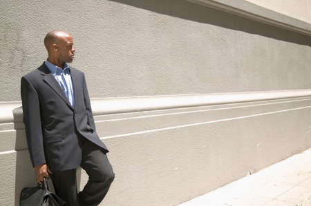 freewill: Mid adult businessman standing leaning against a wall