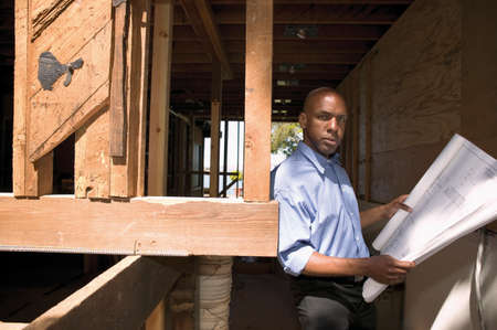 way of behaving: Portrait of a mid adult man standing leaning against a wooden structure holding blue prints