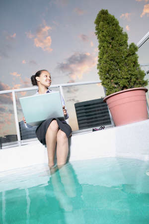 Low angle view of a young businesswoman sitting by a pool with her feet in the water holding a laptop
