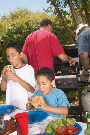 chirpy: Two young boys eating at a barbeque