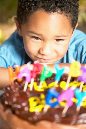 Young boy looking at a birthday cake