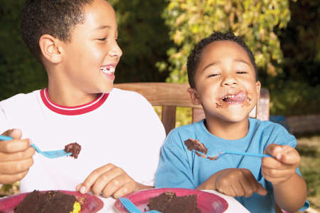 member of the clergy: Two young boys eating cake