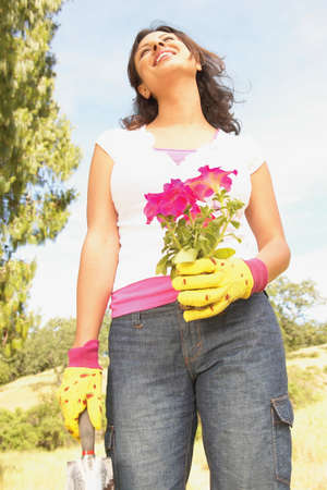 Low angle view of a young woman standing holding a flowering potted plant LANG_EVOIMAGES