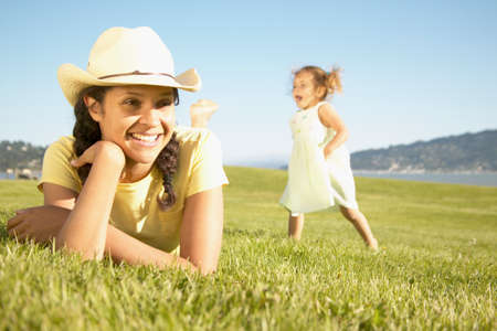 blase: Young woman lying on grass with a young girl running behind LANG_EVOIMAGES
