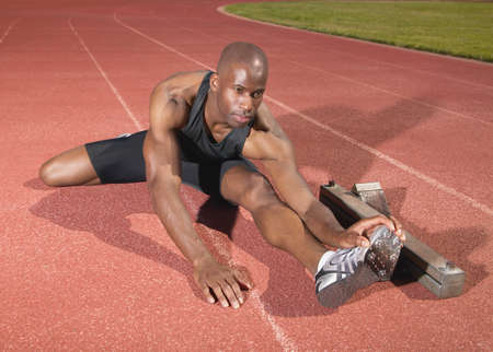 contemplated: Young man stretching on a running track