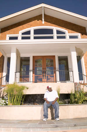 vietnamese ethnicity: Mid adult man sitting in front of a house