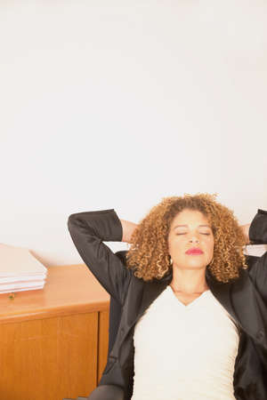 directives: Young businesswoman relaxing on a chair with her hands behind her head