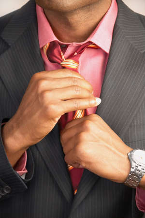 well beings: Young businessman adjusting his tie