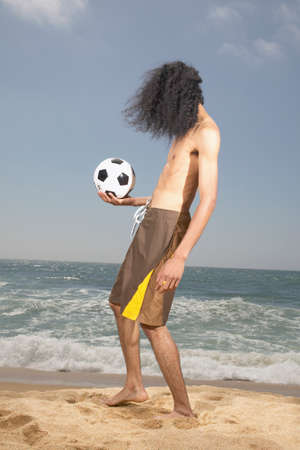 determines: Giovane uomo in piedi sulla spiaggia in possesso di un calcio
