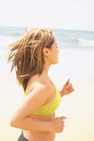 concentrates: Side view of a young woman running at the beach