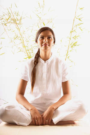Young woman sitting on the floor meditating Stock Photo