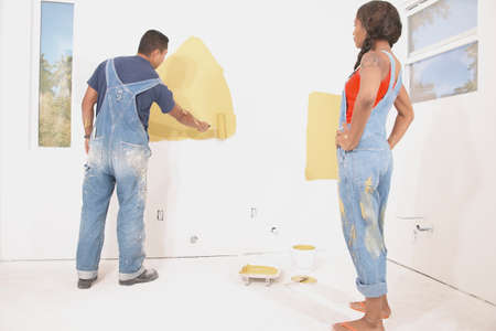 hauteur: Rear view of a young couple painting a wall with a paint roller