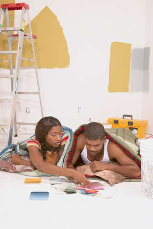 Couple lying in sleeping bags on the floor looking at color samples
