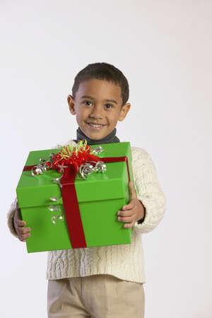 jambes �cart�es: Portrait d'un gar�on tenant un cadeau