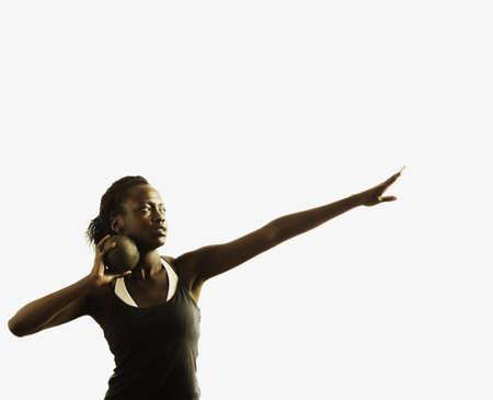 shot put: Mujer joven que sostiene una bola de lanzamiento de peso