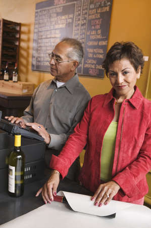 receding hairline: Portrait of a young woman wrapping paper on a wine bottle with a mature man standing beside her