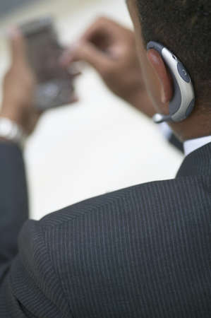 held down: High angle view of a mid adult businessman operating a hand held device