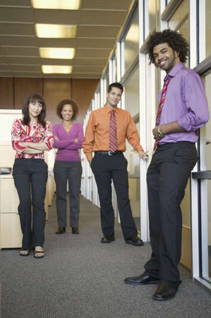 jamaican ethnicity: Two businessmen and two businesswomen smiling LANG_EVOIMAGES