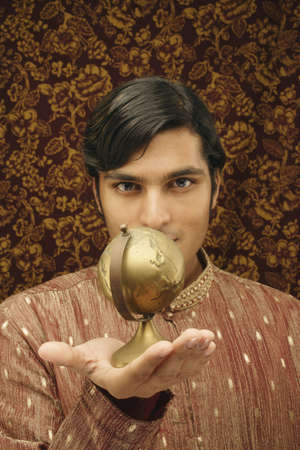 world at your fingertips: Portrait of a young man holding a globe LANG_EVOIMAGES