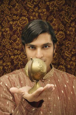 el mundo en tus manos: Retrato de un hombre joven que sostiene un globo LANG_EVOIMAGES