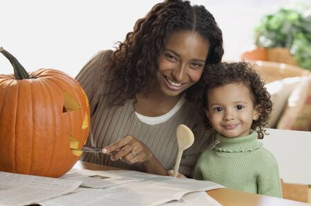 Portrait of a mother carving pumpkin with her daughter