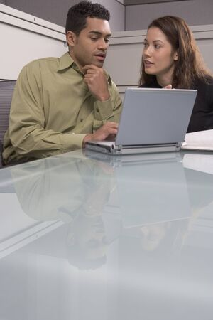 world at your fingertips: Businessman working on a laptop with a businesswoman