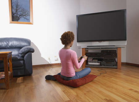 determines: Mid adult woman sitting in front of a television LANG_EVOIMAGES