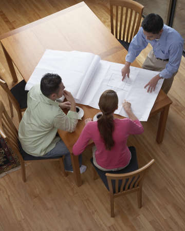 asian architect: High angle view of an architect showing blueprints to a young couple