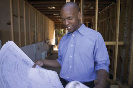 airs: Mid adult man standing holding blue prints