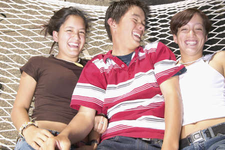 plagiarism: Three young people lying on a hammock and smiling LANG_EVOIMAGES