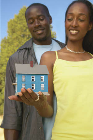 joint effort: Young woman holding a model of a house with a young man standing behind LANG_EVOIMAGES