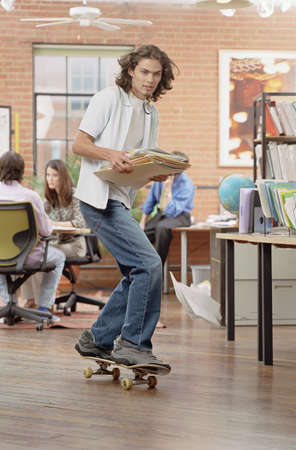 fully unbuttoned: Young man skateboarding holding a file in the library