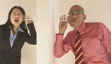 sabotage: Businessman and businesswoman listening with glasses on either side of a wall LANG_EVOIMAGES