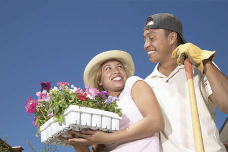 filipino ethnicity: Young couple standing together in a garden holding potted plants smiling