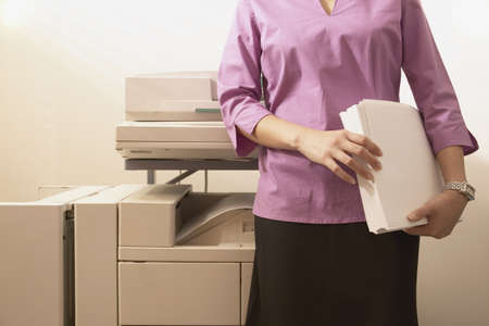 Torso of a young businesswoman standing in front of a copying machine holding stack of paper