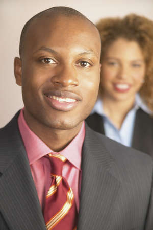 prowess: Portrait of a young businessman smiling with a young businesswoman standing behind LANG_EVOIMAGES