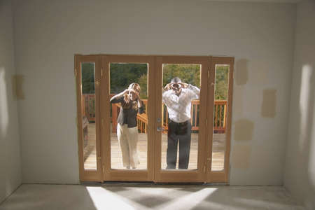 remoteness: Young couple peering through a glass window of an un occupied house LANG_EVOIMAGES